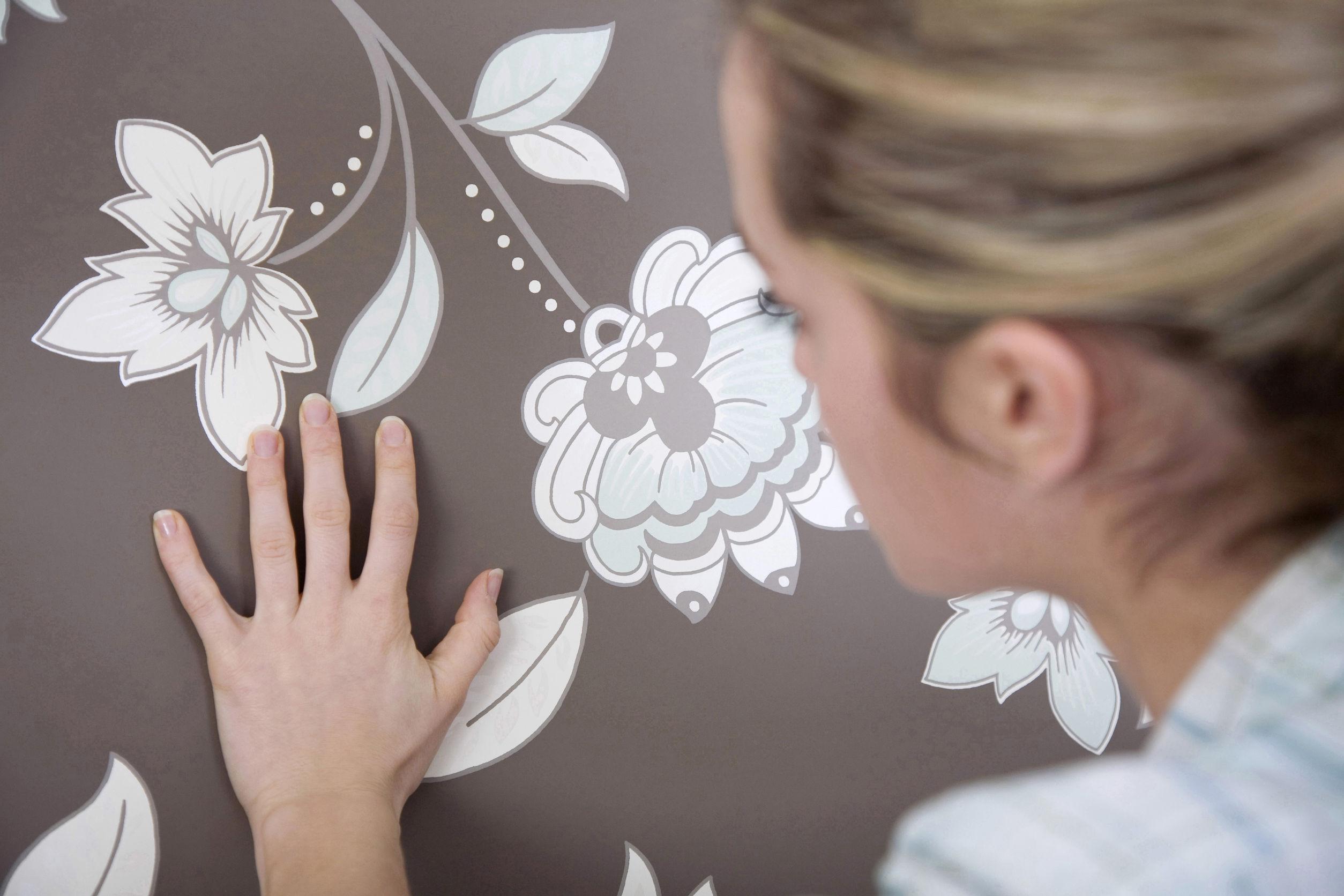 Imagem de uma mulher aplicando papel de parede.