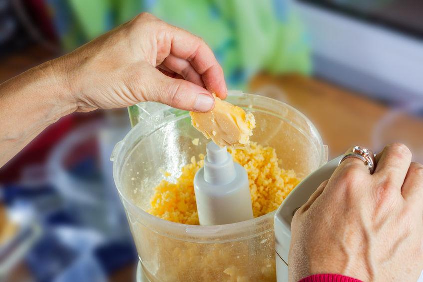 Na foto uma pessoa colocando manteiga em um processador de alimentos.
