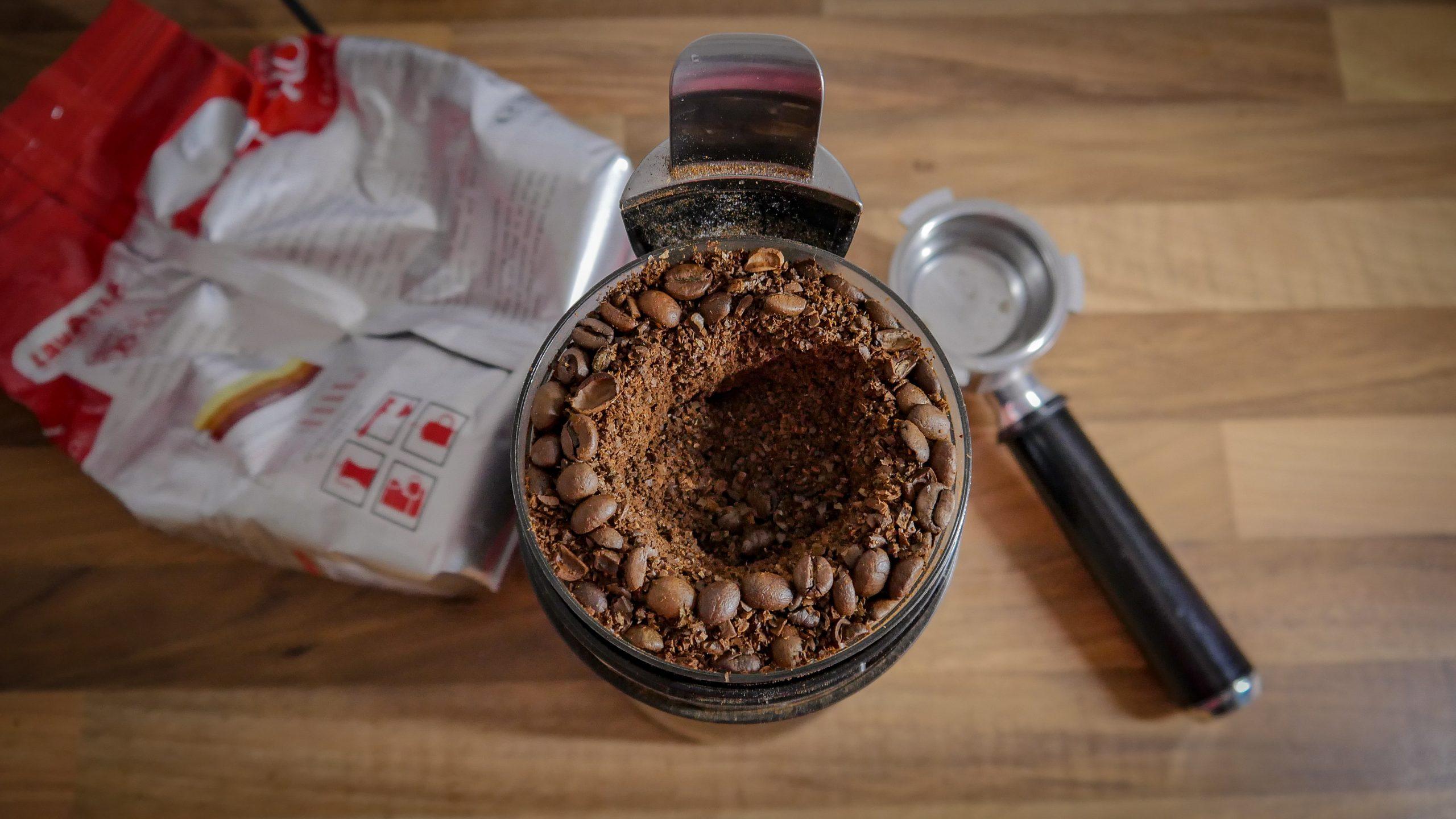 Na foto um moedor de café com um saco de papel ao fundo.