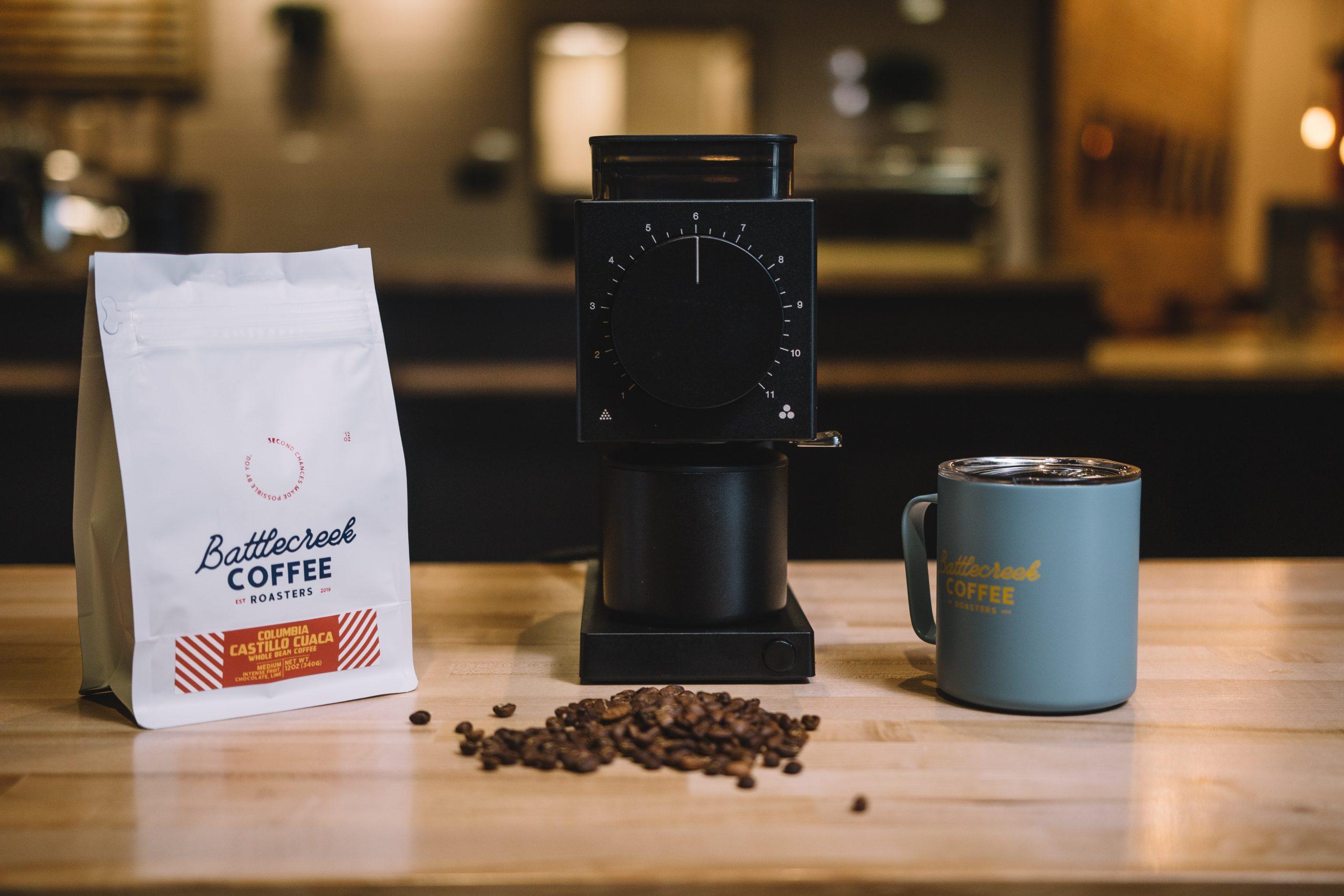 Na foto um moedor de café ao lado de um pacote de café e uma xícara.