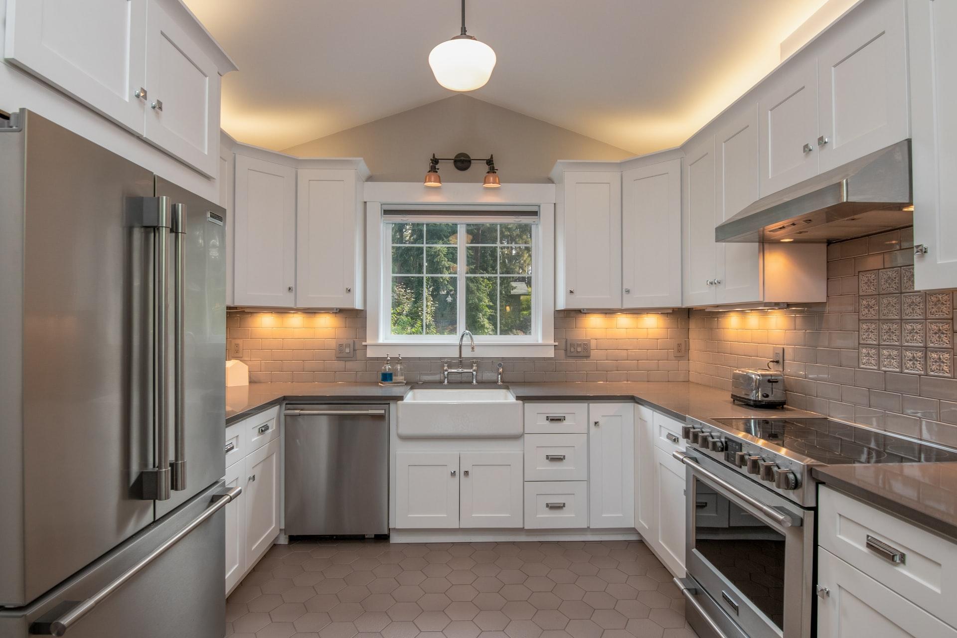 Na foto uma cozinha com armários brancos e eletrodomésticos em aço inox.