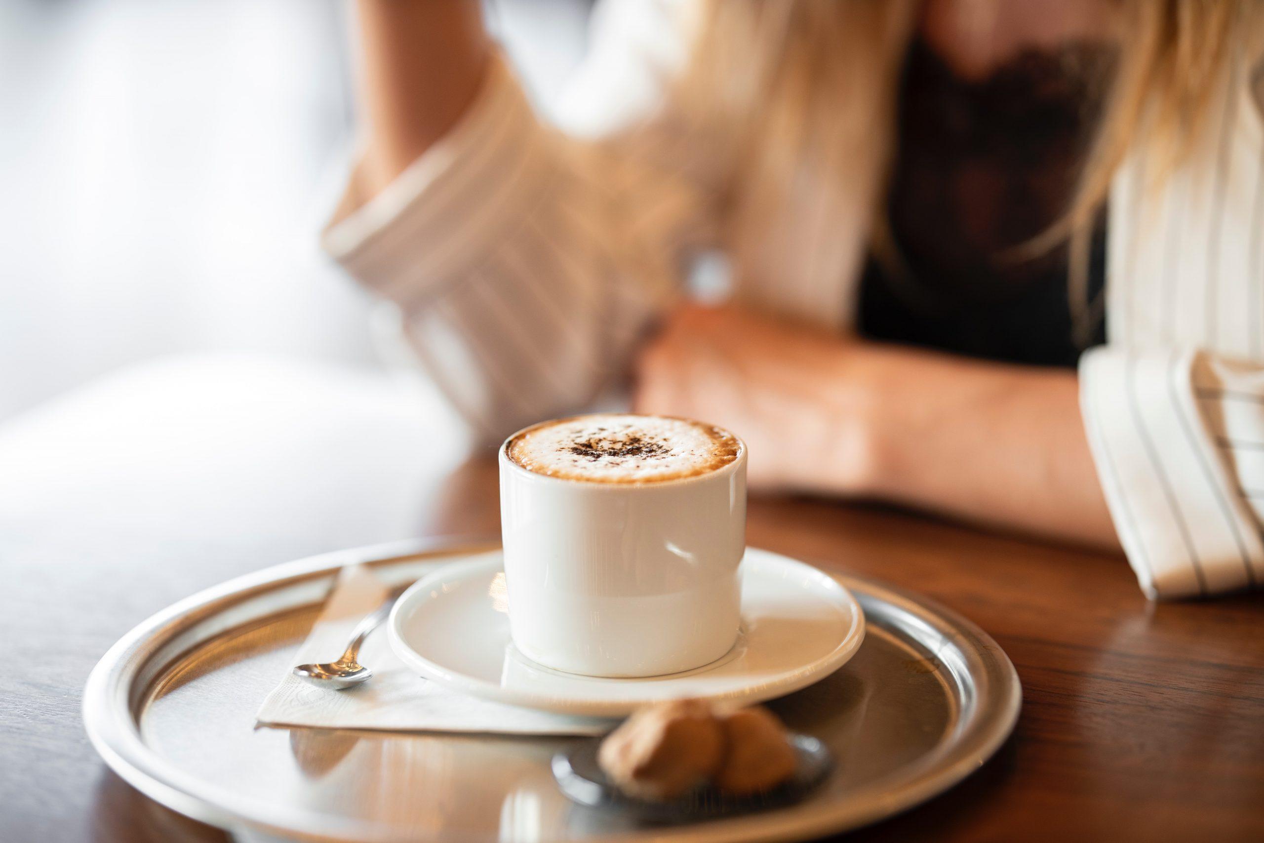 Na foto uma xícara de café em cima de uma mesa com uma mulher ao fundo.