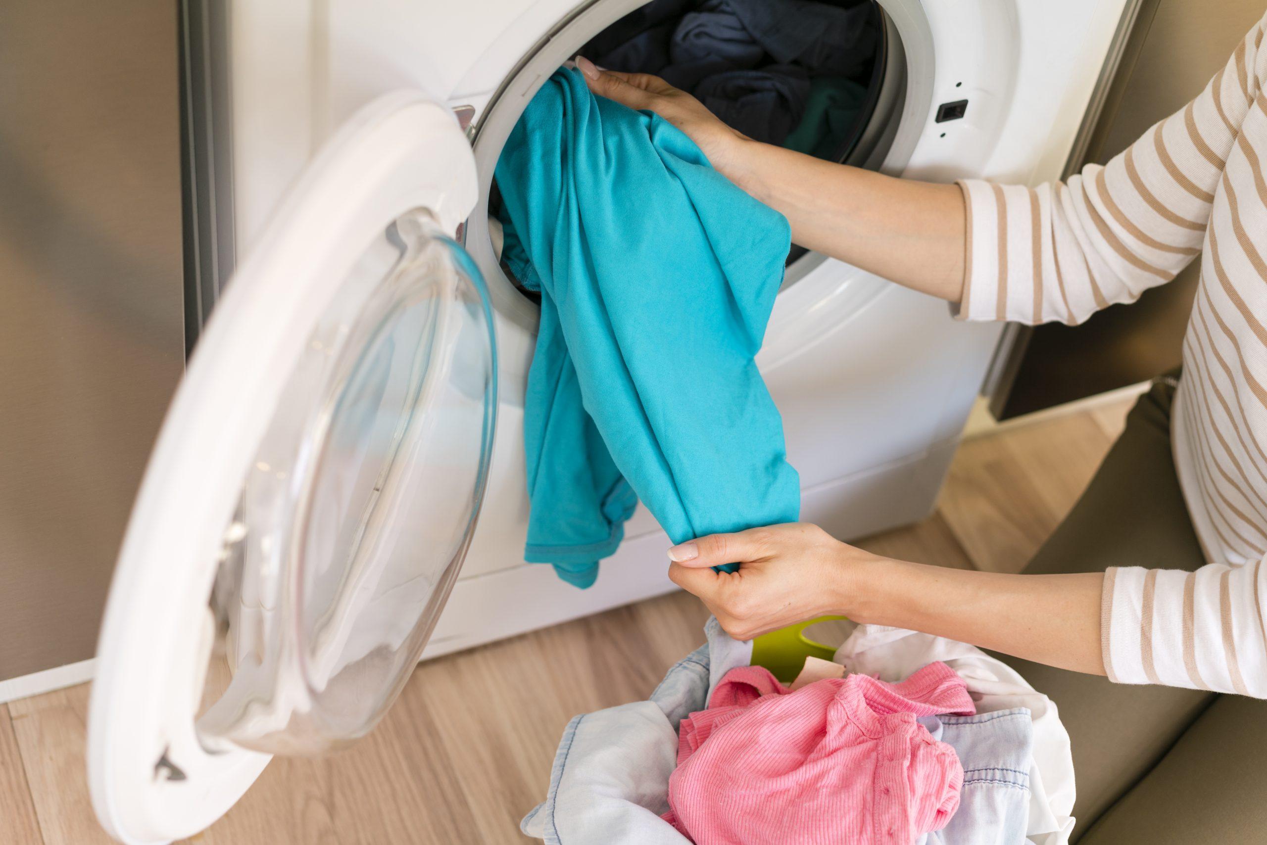 Mulher tirando roupas da máquina de lavar.