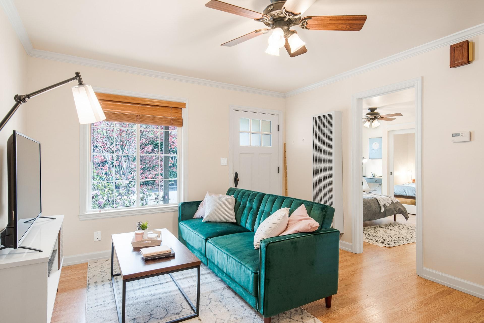 Na foto uma sala de estar com sofá turquesa e ventilador de teto.