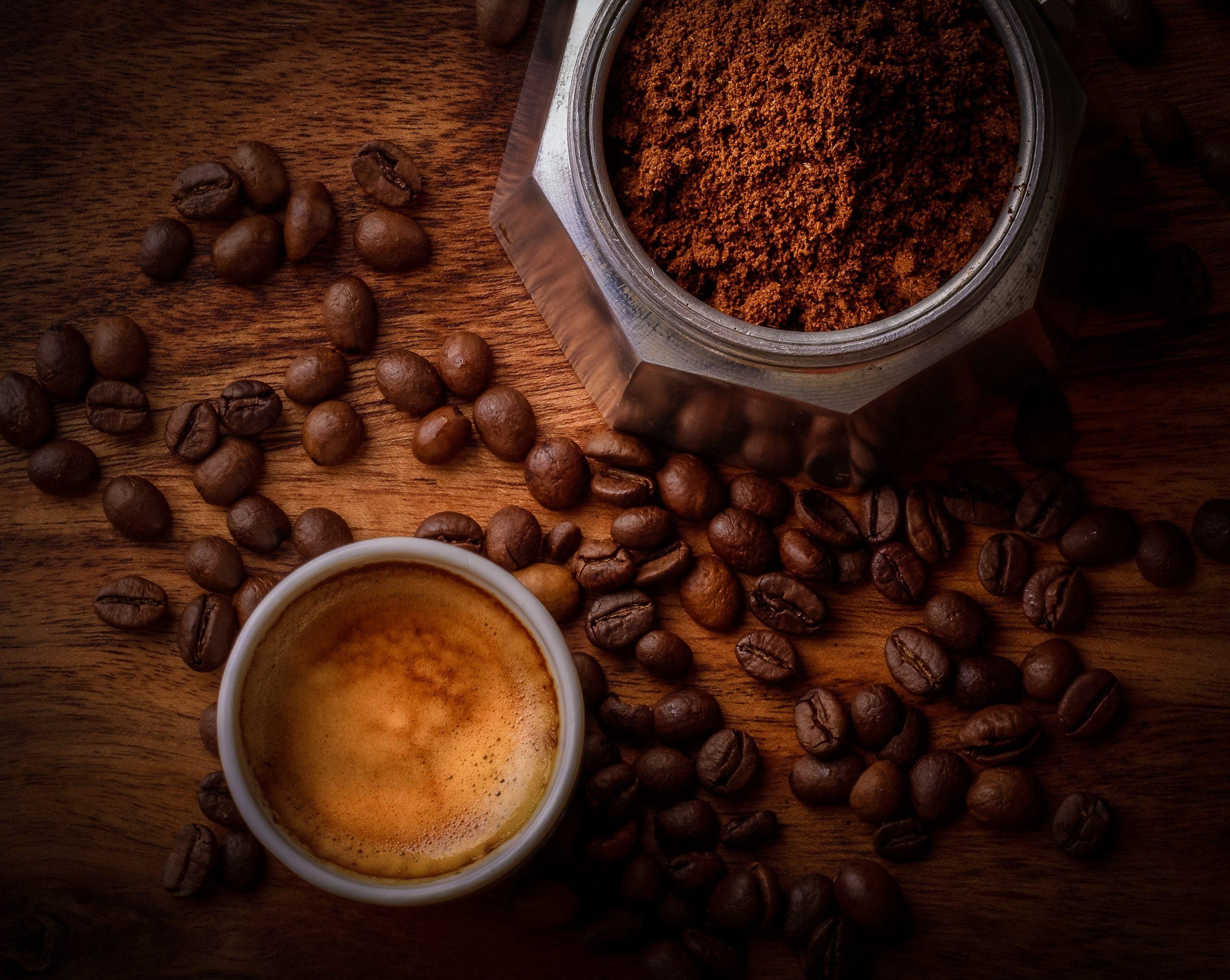 Na foto uma xícara com café, alguns grãos de café espalhados e um pote com pó de café.