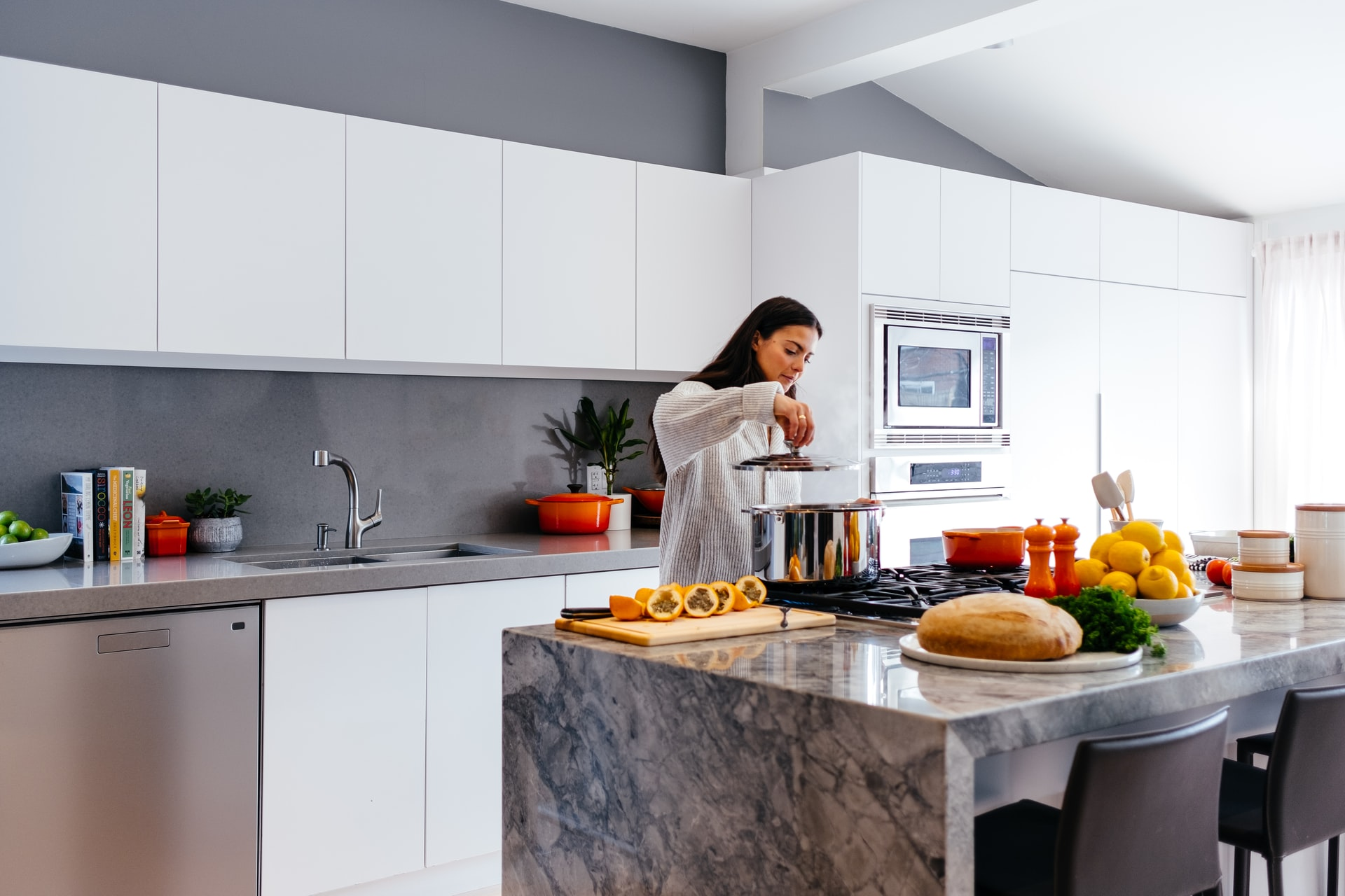 Na foto uma mulher cozinhando em uma cozinha grande com ilha.