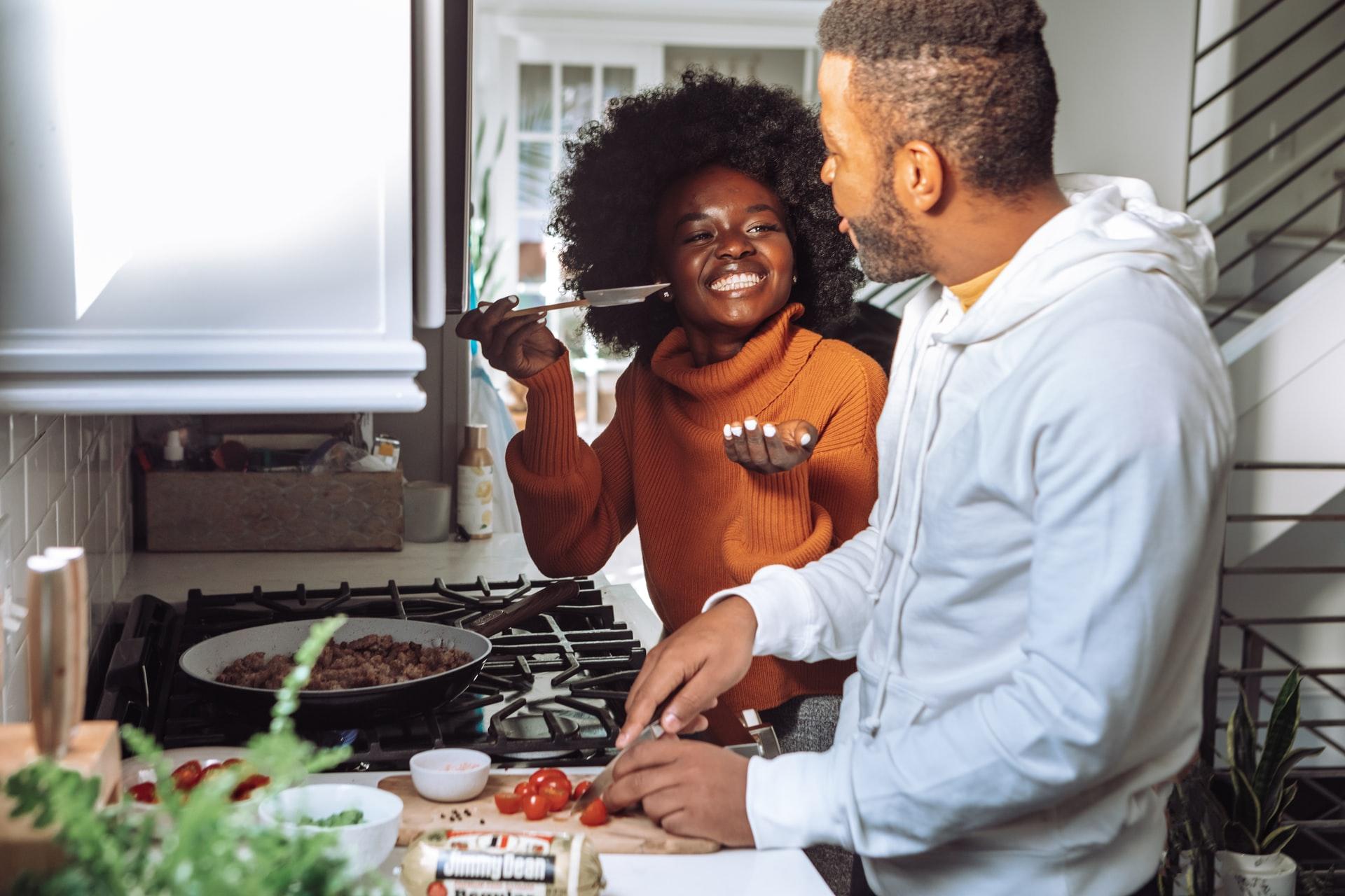 Na foto um casal cozinhando juntos em uma cozinha pequena.
