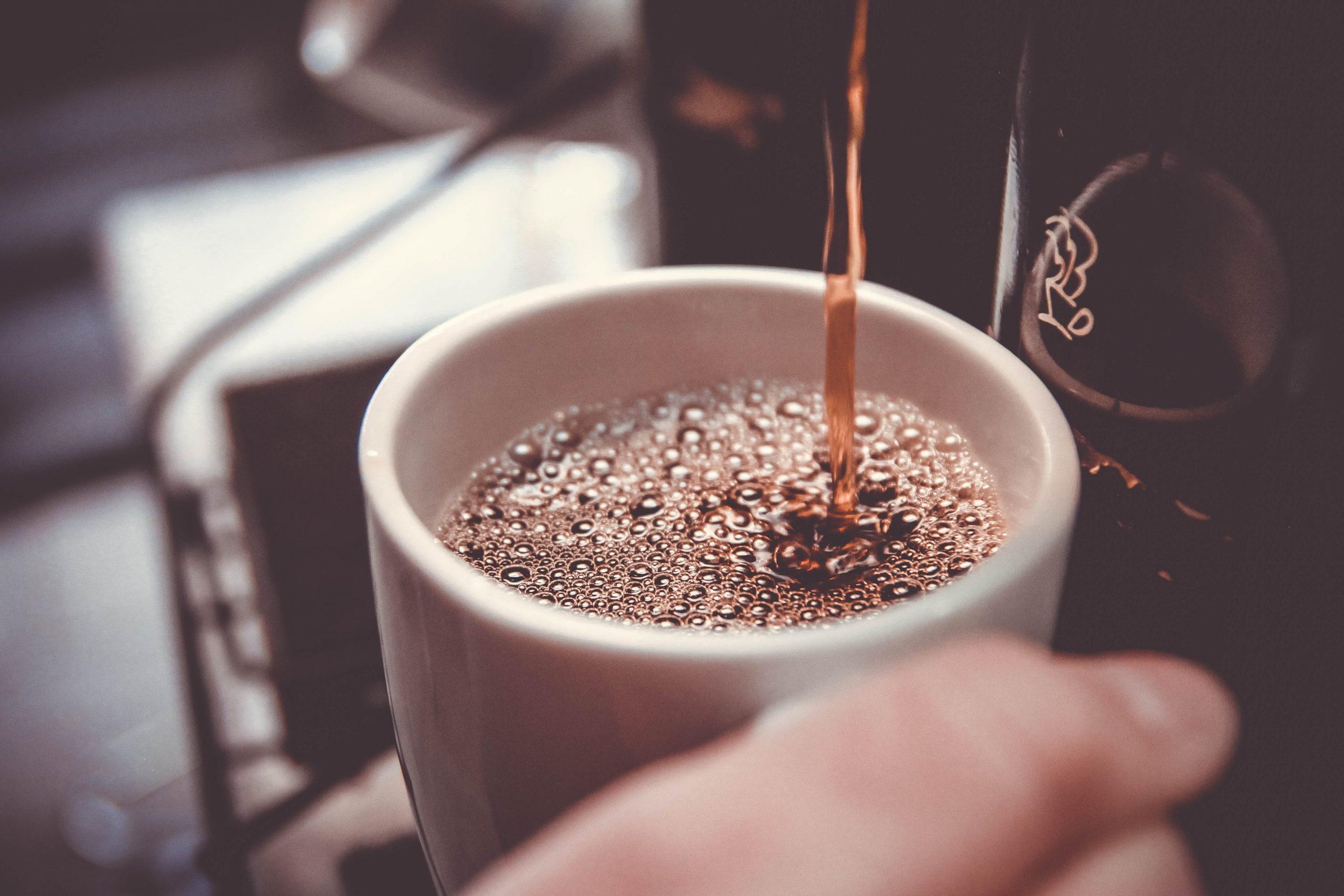 Na foto uma pessoa segurando uma xícara de café em uma cafeteira.
