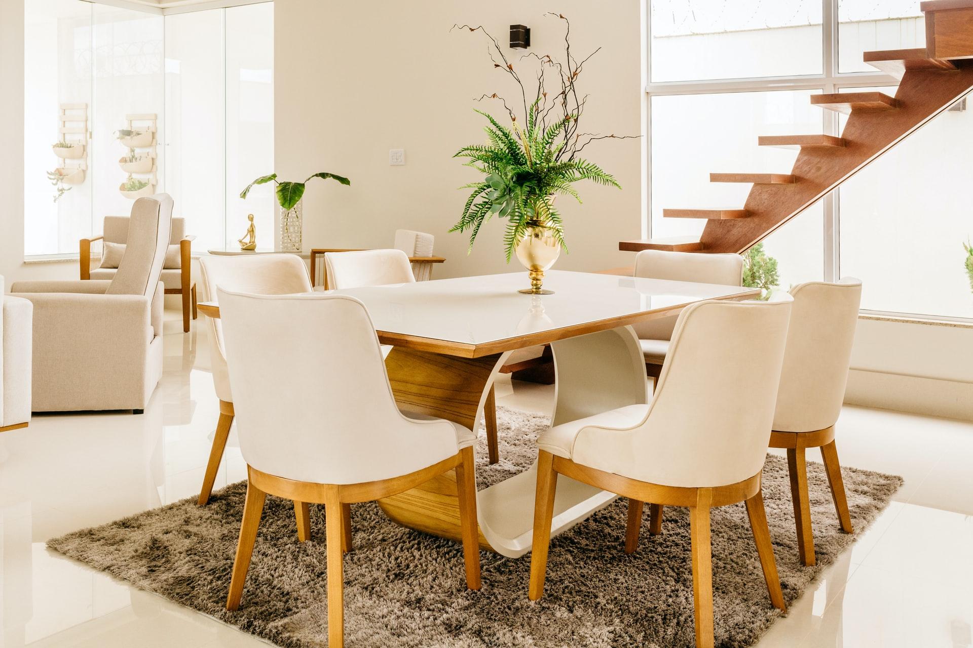 Na foto uma mesa de jantar de madeira com tampo de vidro com uma escada ao fundo.
