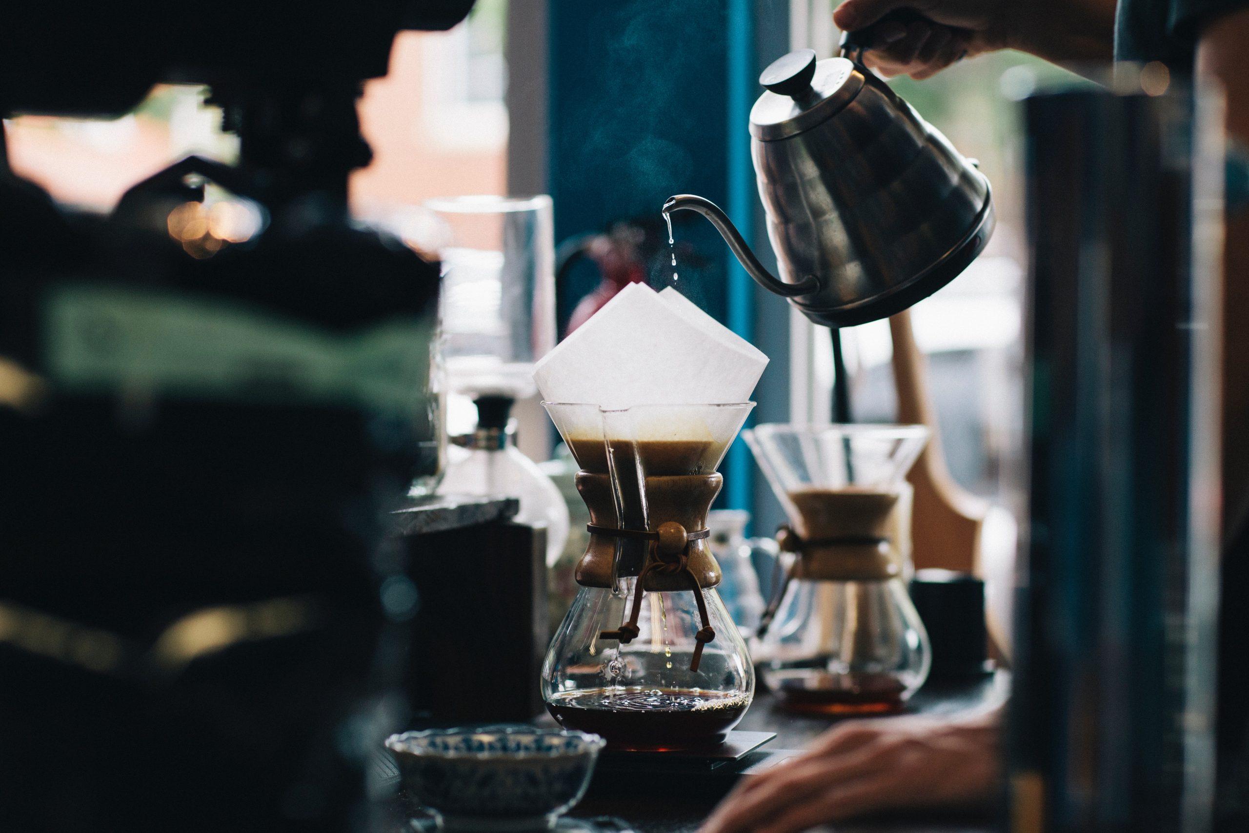 Na foto uma pessoa passando café em um filtro de papel.