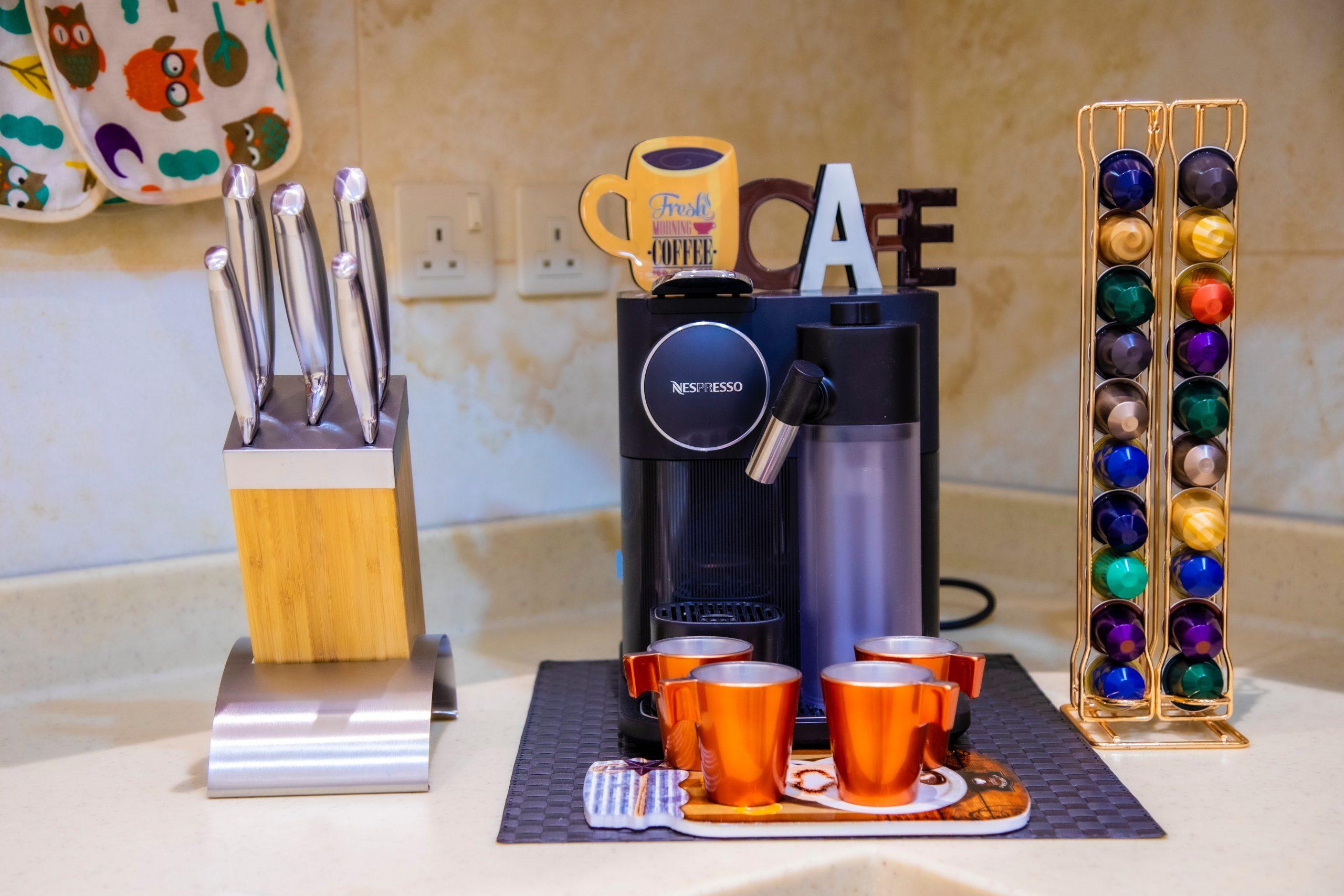 Na foto uma cafeteira Nespresso ao lado de um porta cápsulas, xícaras e um porta facas.