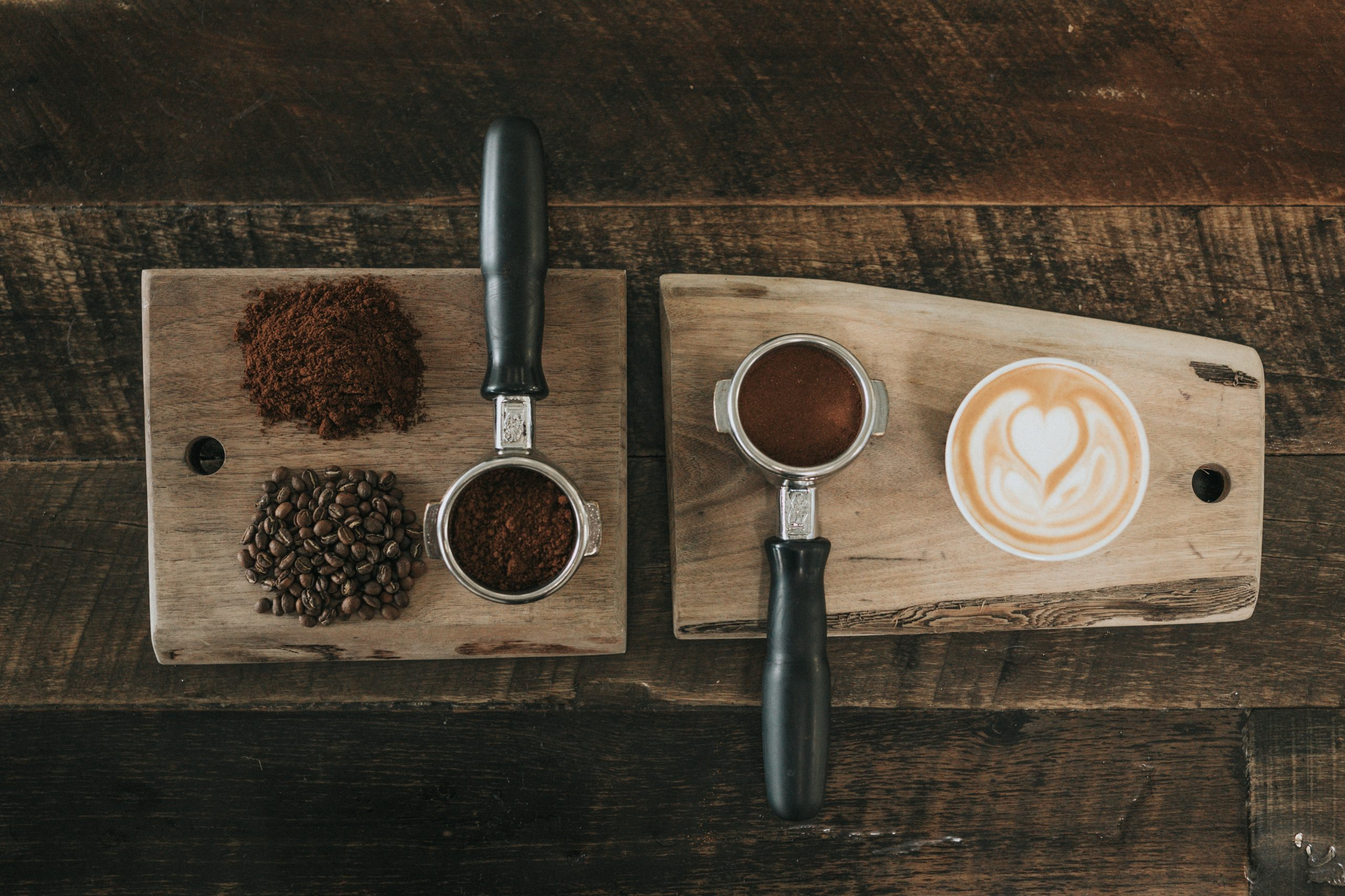 Na foto duas tábuas de madeira com pós e grãos de café e uma xícara com café dentro.