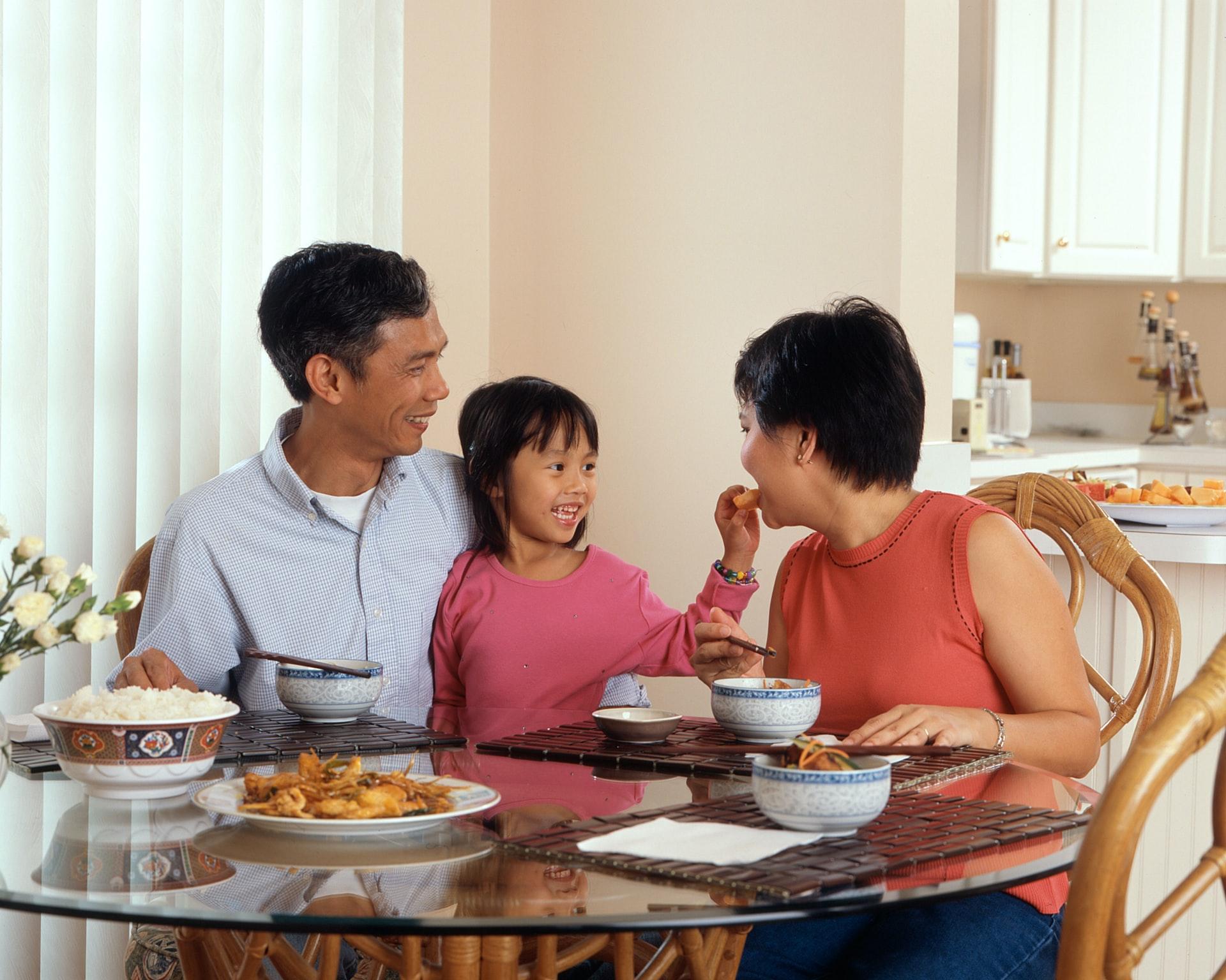 Na foto uma família sentada em uma sala de jantar.