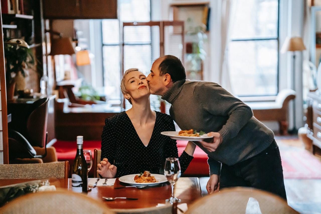 Na foto uma mulher sentada recebendo um beijo na bochecha de um homem com um prato de macarrão na mesa.