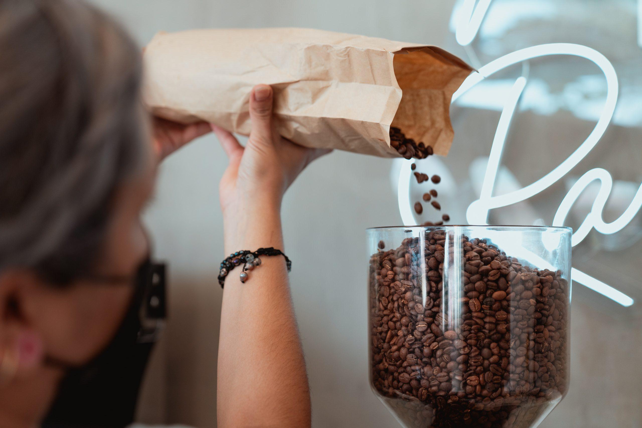 Na foto uma mulher despejando grãos de café em um moedor.