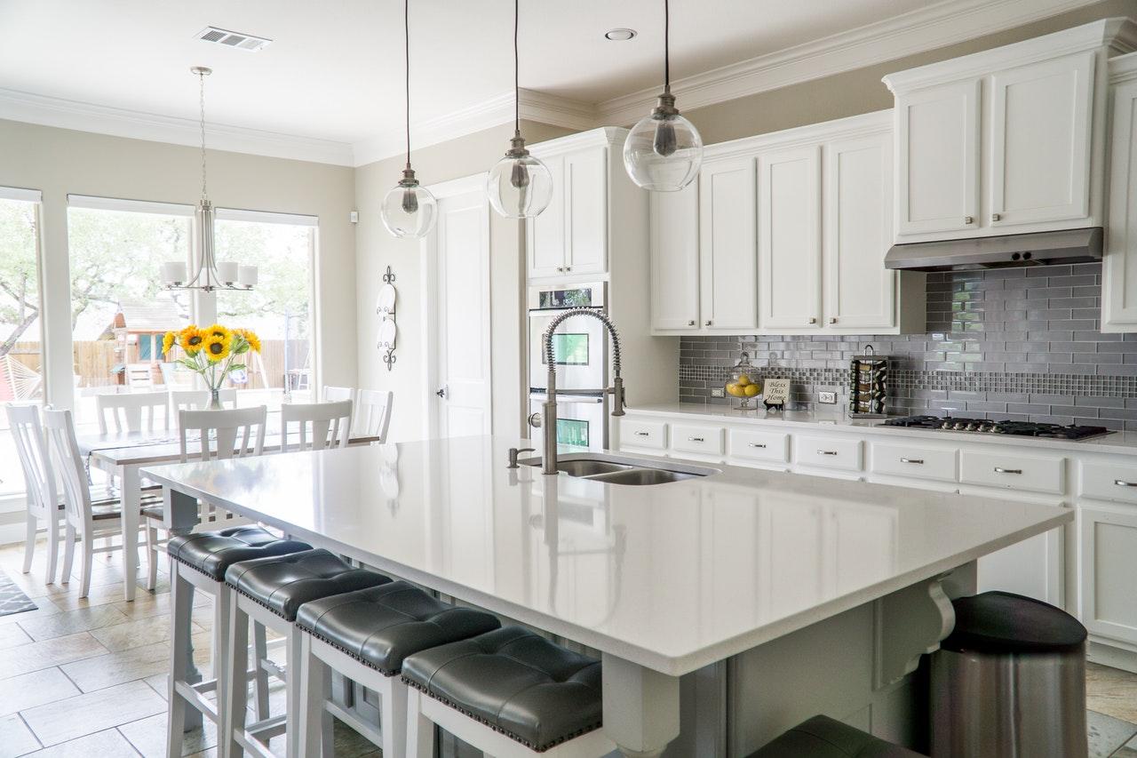 Na foto uma cozinha com armários brancos, ilha de mármore com bancos com estofado cinza.