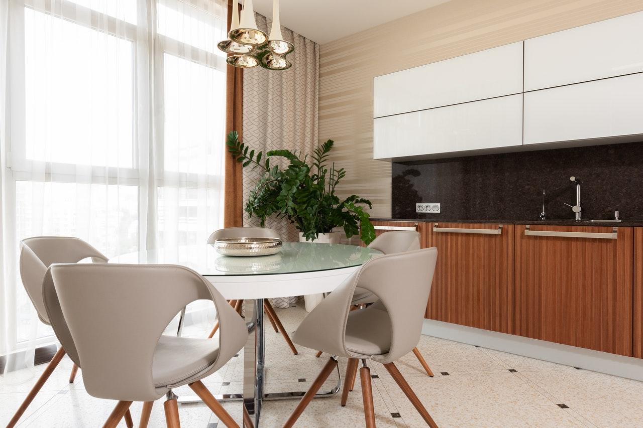 Na foto uma sala de jantar com uma mesa redonda e cadeiras também redondas em cinza.