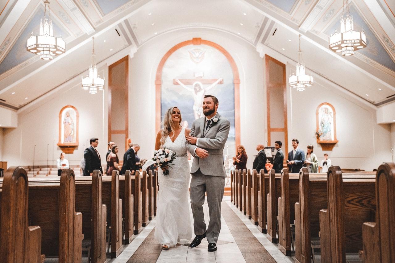 Na foto um casal de noivos saindo de uma igreja com os convidados ao fundo.