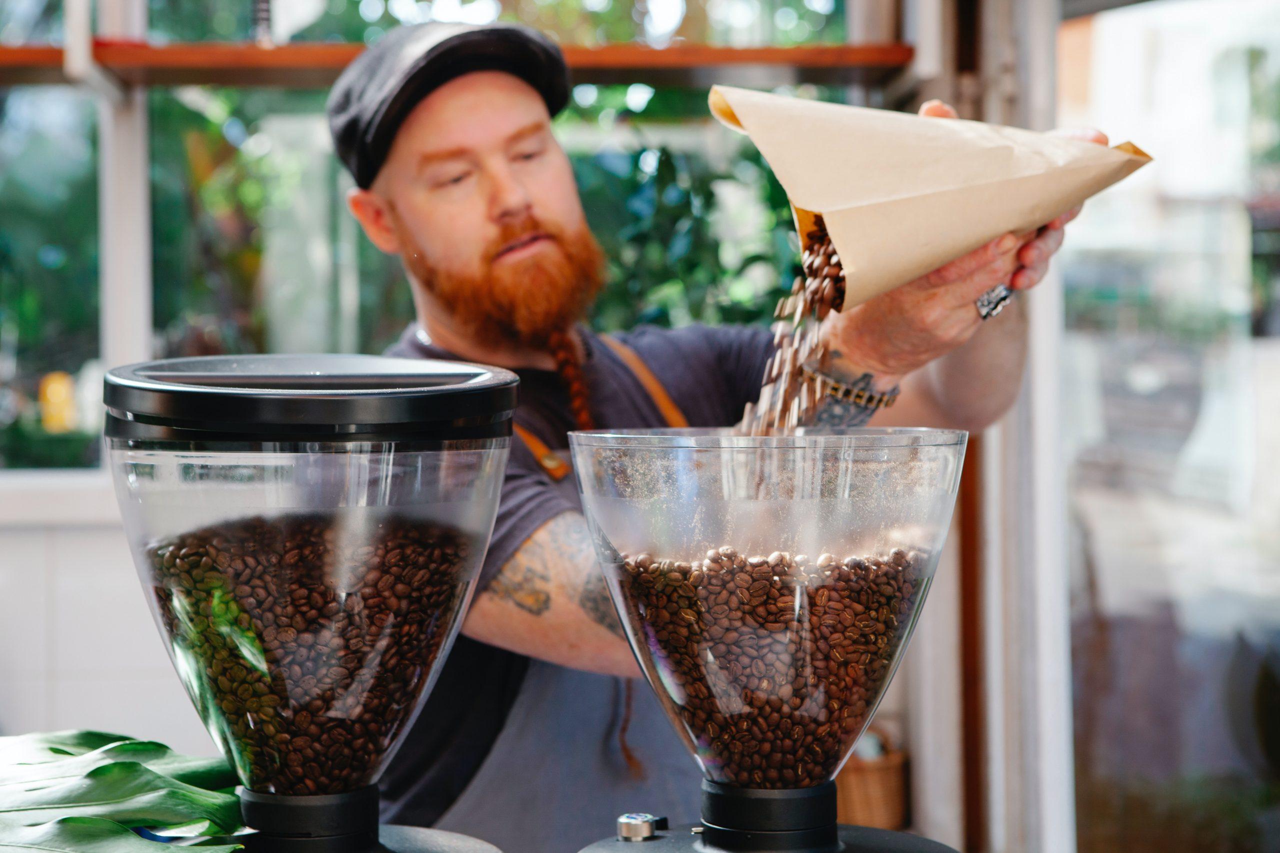 Na foto um homem colocando grãos de café no reservatório de um moedor de café.