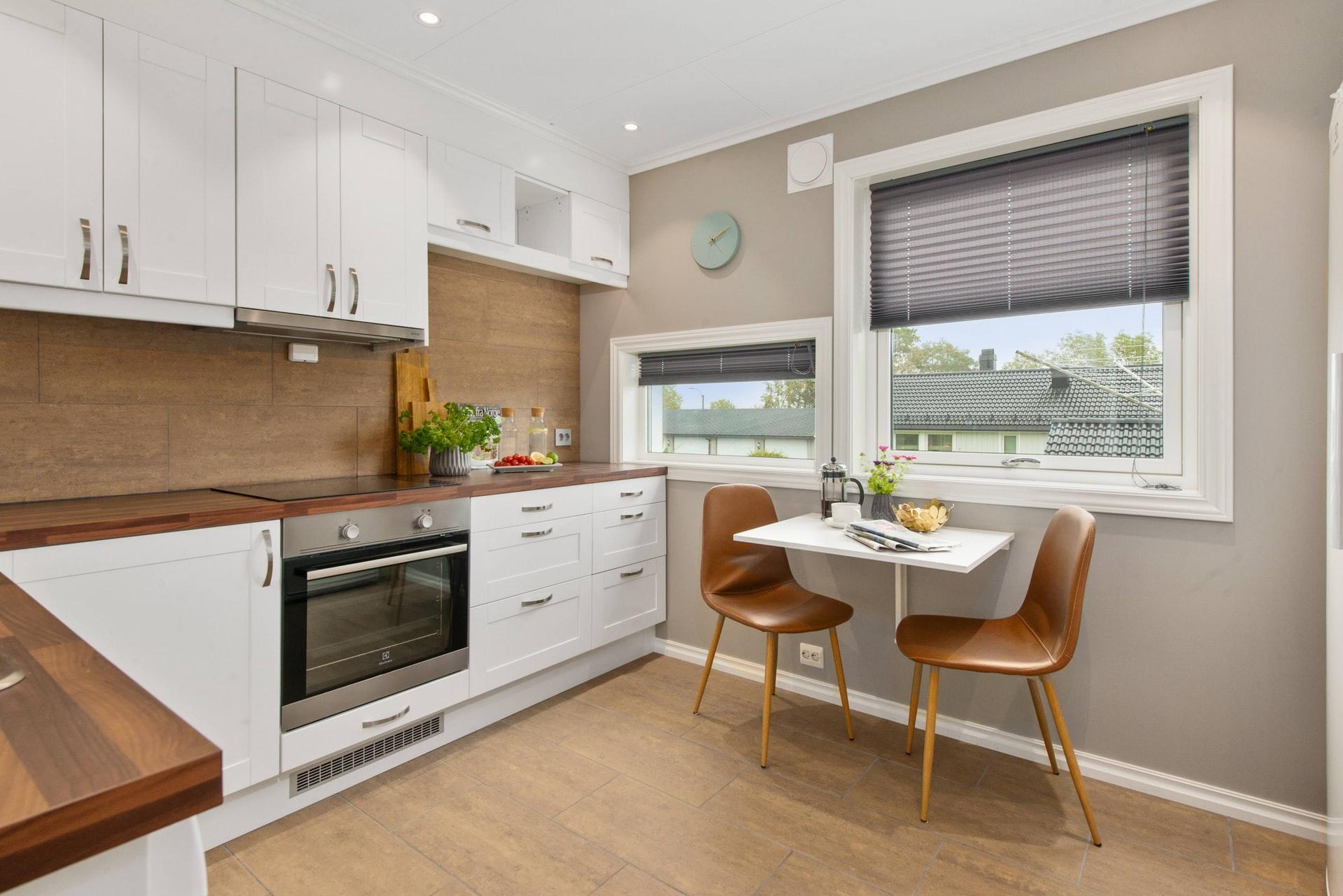 Na foto uma cozinha pequena com uma bancada de madeira e uma mesa com duas cadeiras.