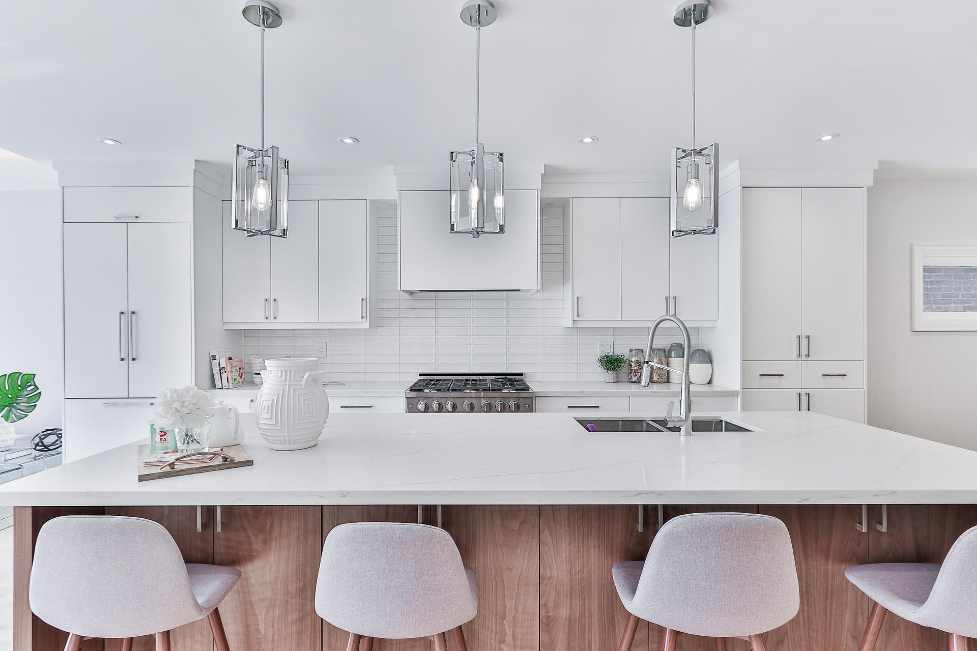 Na foto uma cozinha com armários brancos e uma ilha com três pendentes sobre a ilha.
