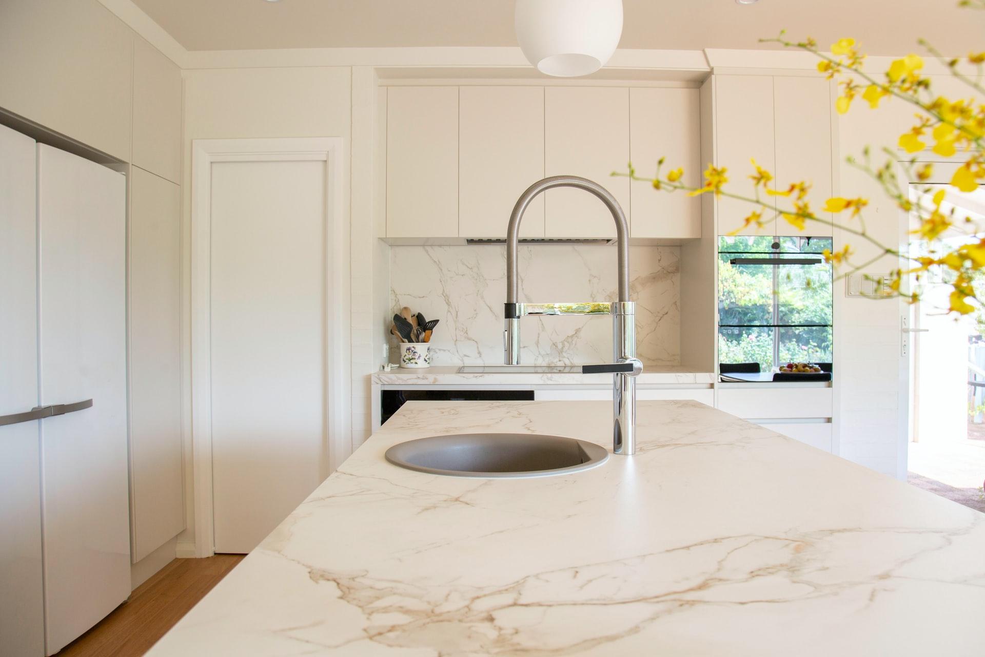 Na foto uma cozinha com bancada de mármore e flores amarelas.