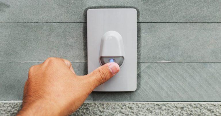 Na foto o dedo de um homem apertando uma campainha instalada em uma parede cinza.