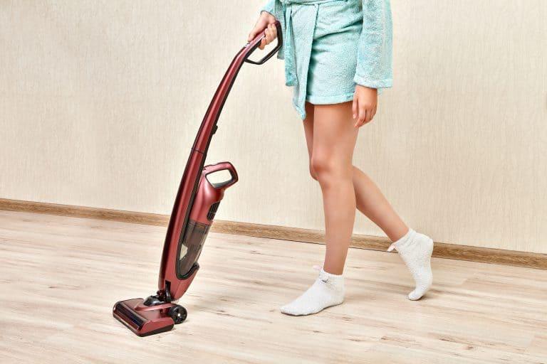 Mulher usando aspirador de pó vertical sem fio.