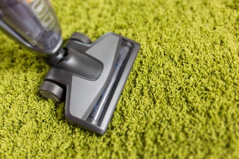 Aspirador de pó sobre tapete verde.