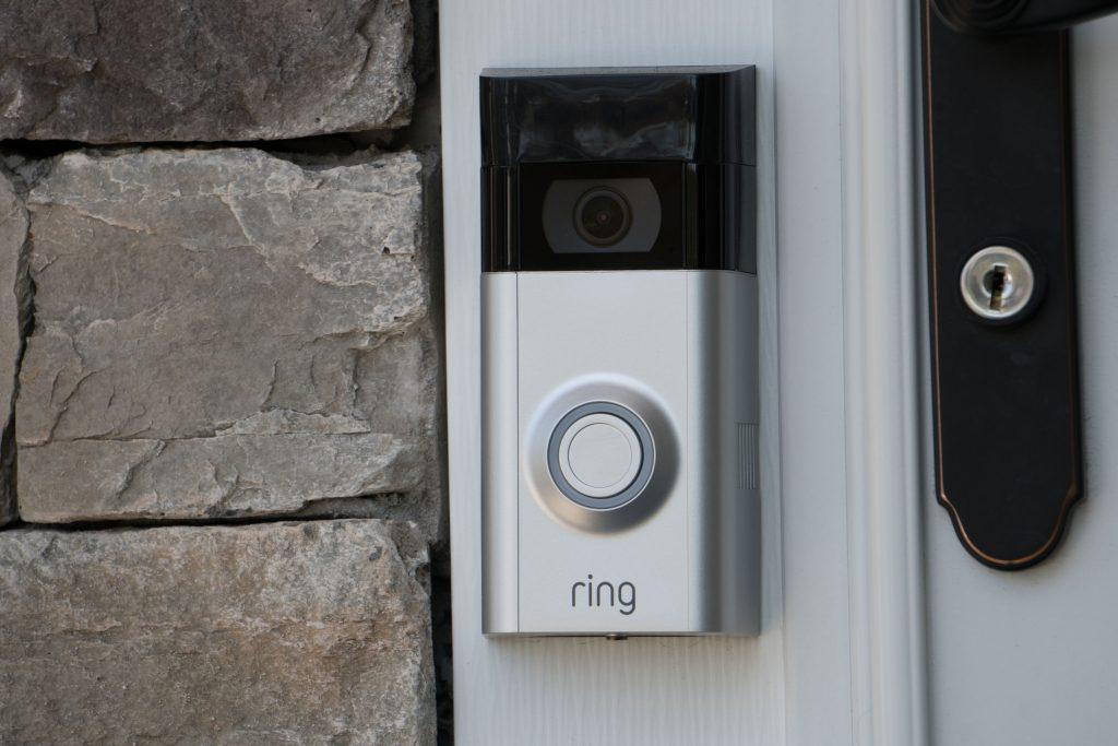 Na foto uma campainha sem fio com câmera instalada em uma porta de metal.
