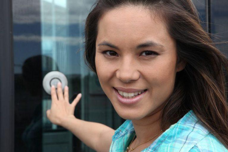 Na foto uma mulher olhando para a foto tocando uma campainha em uma porta de vidro.