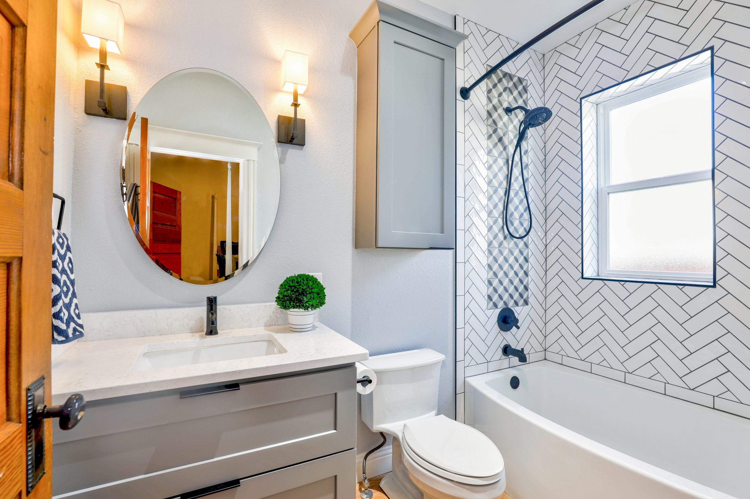 Na foto um banheiro com armários, banheira, chuveiro e um espelho oval.