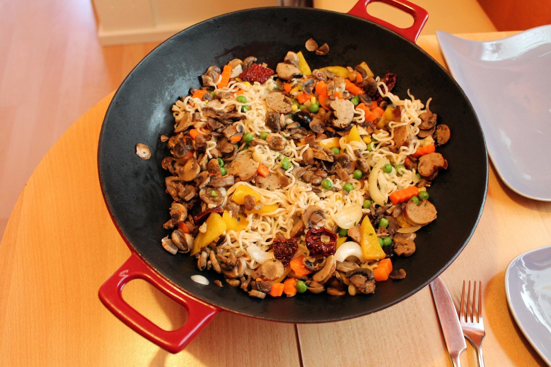 Panela wok com refogado de legumes, cogumelos e macarrão asiátio.