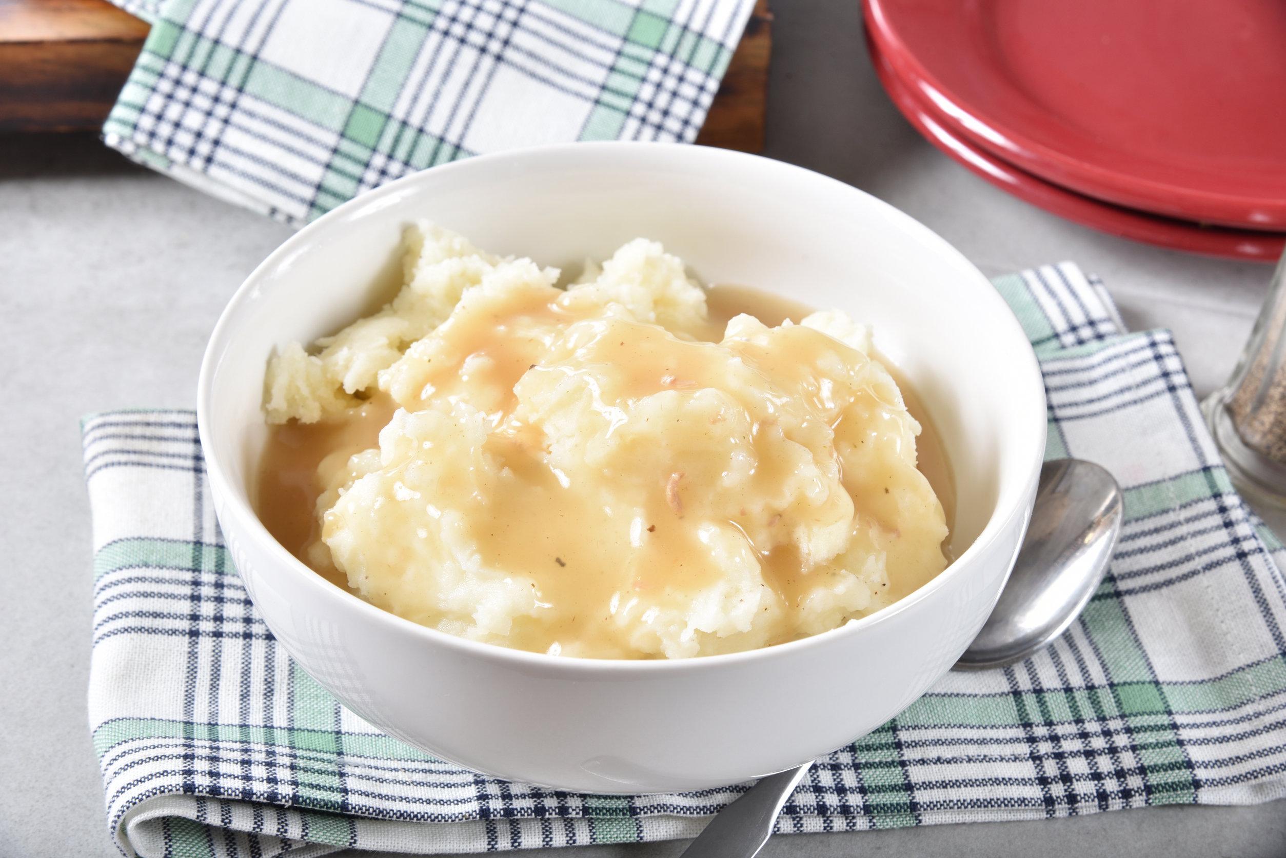 Uma tigela de puré de batata coberta com molho de galinha